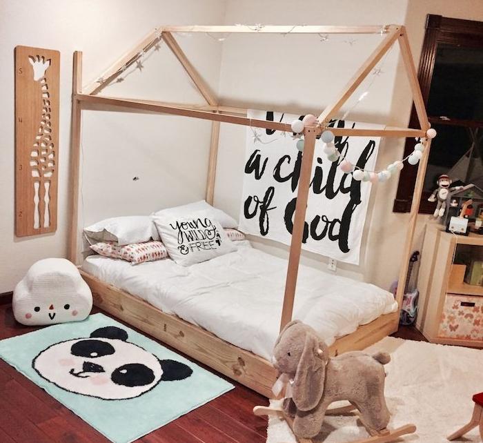 murs blancs, lit en bois enfant style maisonnette, parquet bois foncé, murs blancs, cheval à bascule, tapis enfant panda mignon