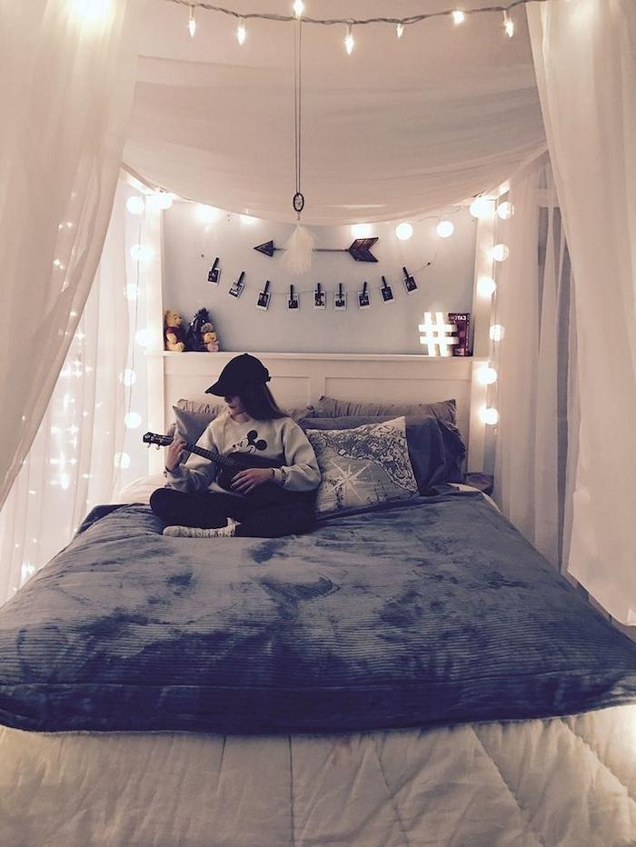 Quelle deco chambre ado choisir, chambre tumblr avec beaucoup de guirlandes lumineuses, fille qui joue à la guitare assise sur son lit cozy