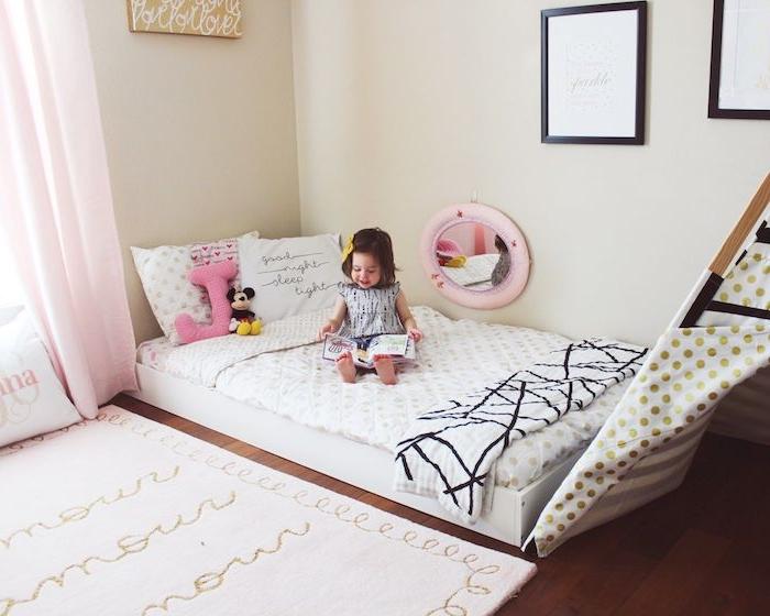 lit au sol montessori avec un tipi cabane sur parquet marron, tapis blanc à texte, murs couleur beige, amenagement chambre fille