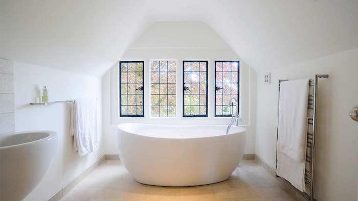 baignoire blanche dans une salle de bain en blanc avec carrelage beige clair, murs blancs, fenetres encadrement noir