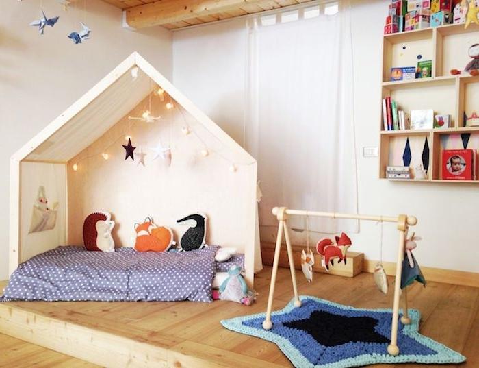 lit maisonnette bois avec matelas, guirlande lumineuse et coussins enfant animaux, parquet bois, tapis d'éveil montessori en forme d étoile