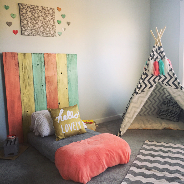 lit au sol matelas avec tete de lit en planches de palette, tipi enfant noir et blanc, tapis gris, murs gris