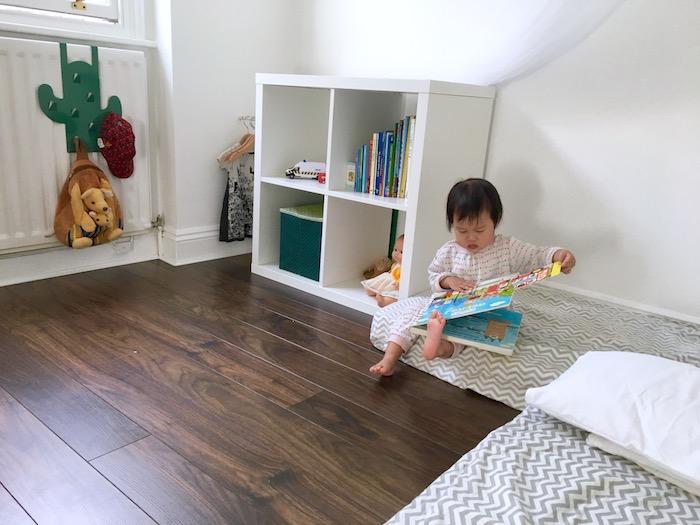 deux lits au sol avec couverture chevron gris et blanc, parquet marron, étagère kallax livres et jouets