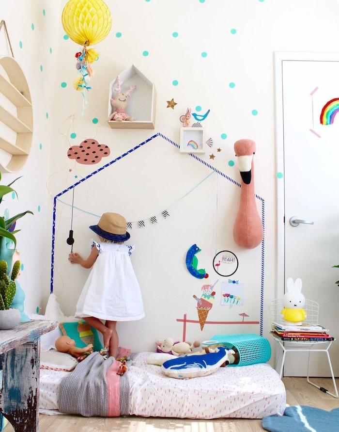 mur décoré d un motif maison en washi tape et autres petites decorations, matelas au sol, petite fille qui joue