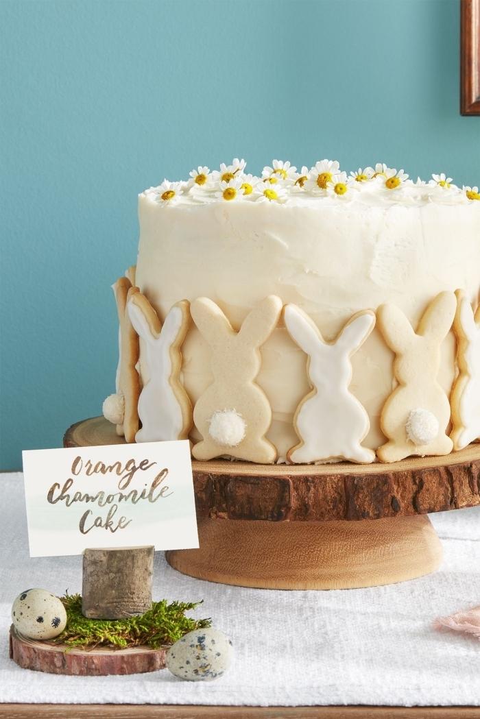 gâteau sur le thème de pâques orange et camomille, recouvert de glaçage crème beurre décoré de petits sables au glaçage blanc en forme de lapins