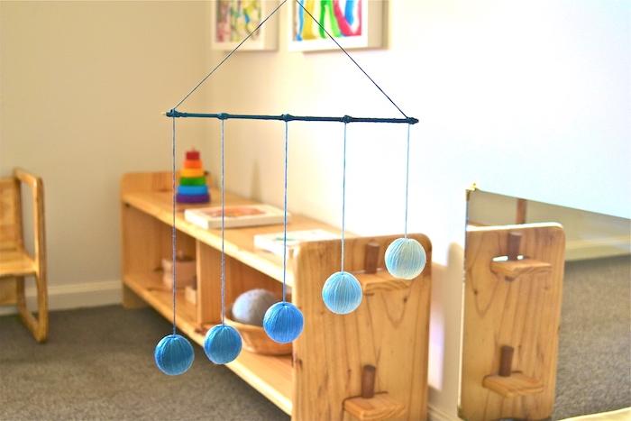 mobile montessori à suspendre dans la chambre enfant, exemple balle montessori garcon en balles bleues, mobilier bois