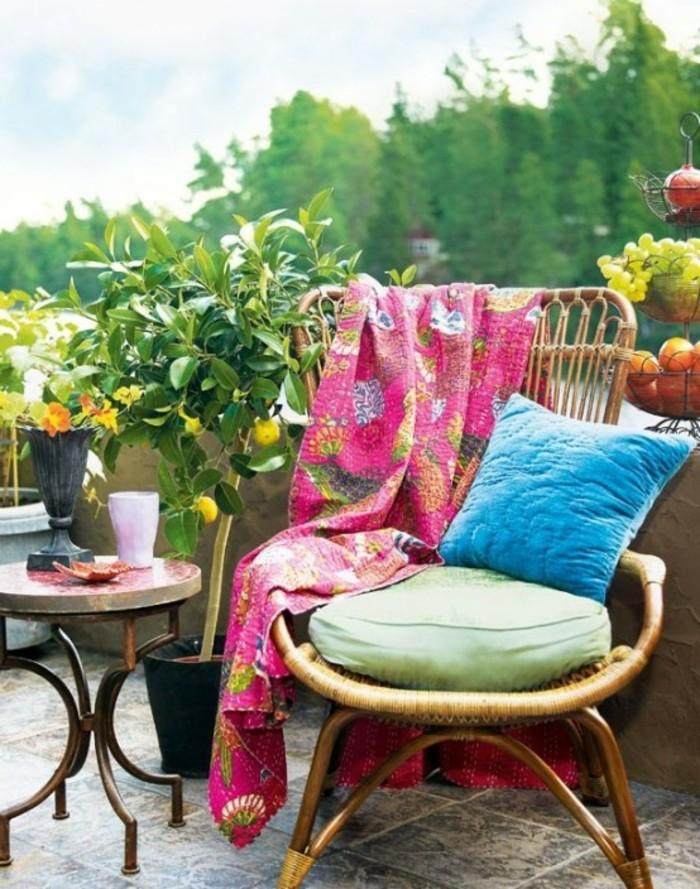 chaise tressée décoré d un coussin bleu, table basse ronde sur une terrasse en carrelage marron et gris, plantes exotiques