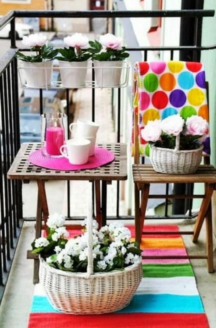 table et chaise en bois, plantes en pots blancs, panier à fleurs sur tapis à rayures colorées, terrasse design