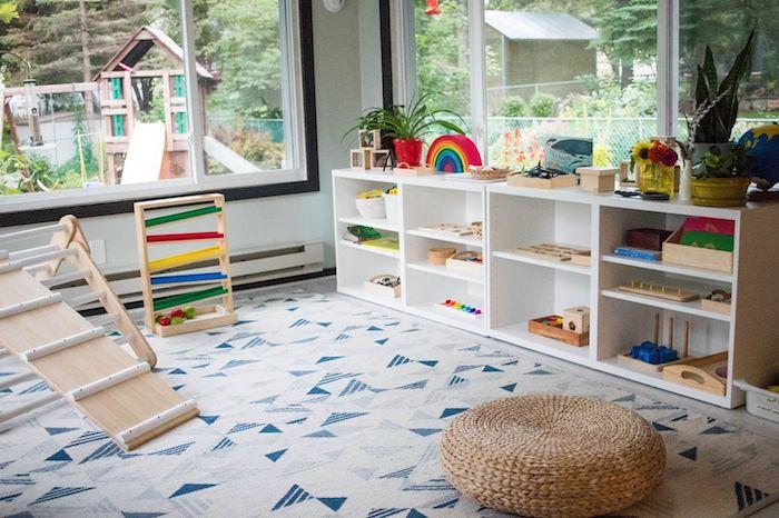aire de jeux à la maison avec des jouets montessori, tapis à triangles bleu et gris, etagere jouets basse, pouf jonc de mer
