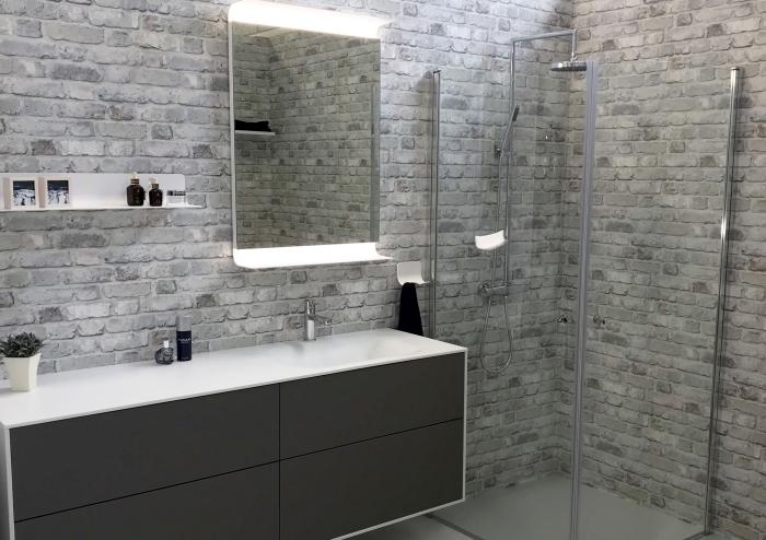 modèle de salle de bain grise aux murs effet briques avec meuble moderne en blanc et gris foncé mate, astuce gain place rangement mural