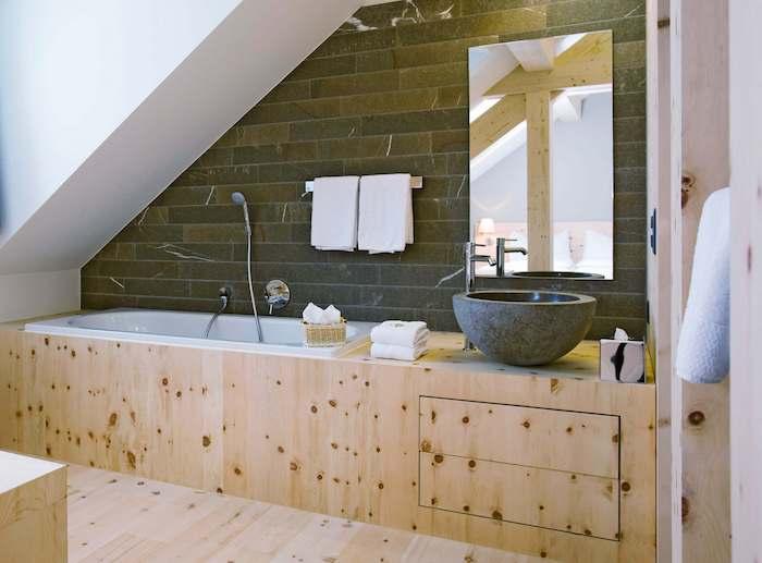 baignoire sous comble avec revêtement de bois, idée de vasque à poser en pierre sur meuble salle de bain bois, mur d accent imitation pierre, miroir rectangulaire