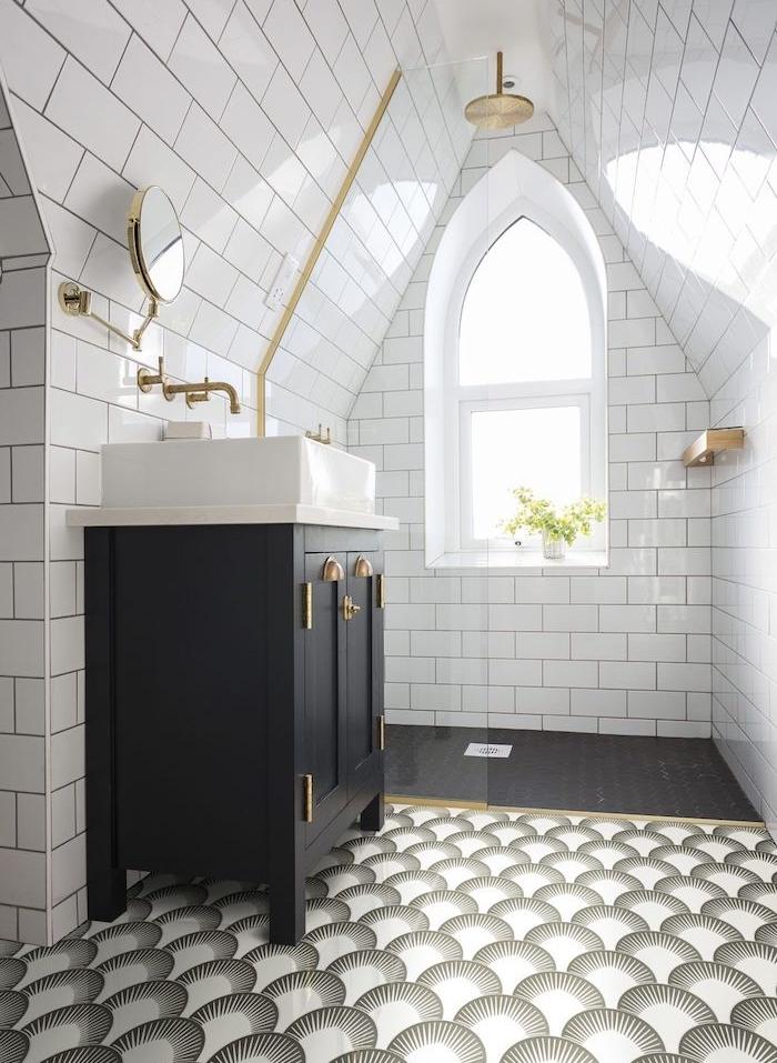 salle de bain mansardée avec douche en laiton, carrelage noir et carrelage décoratif, meuble salle de bain noir avec vasque à poser blanche, murs en carrelage metro blanc