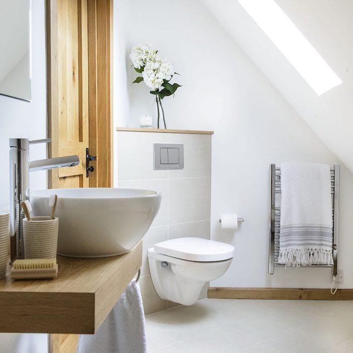 salle de bain en carrelage gris clair, murs blancs, vasque sur planche bois flottante, wc suspendu, salle de bain moderne