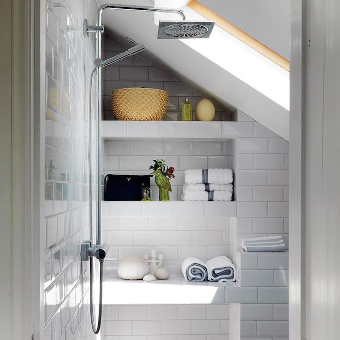 salle de bain avec carrelage blanc et rangement sous pente, étagères en niche murale, douche simple