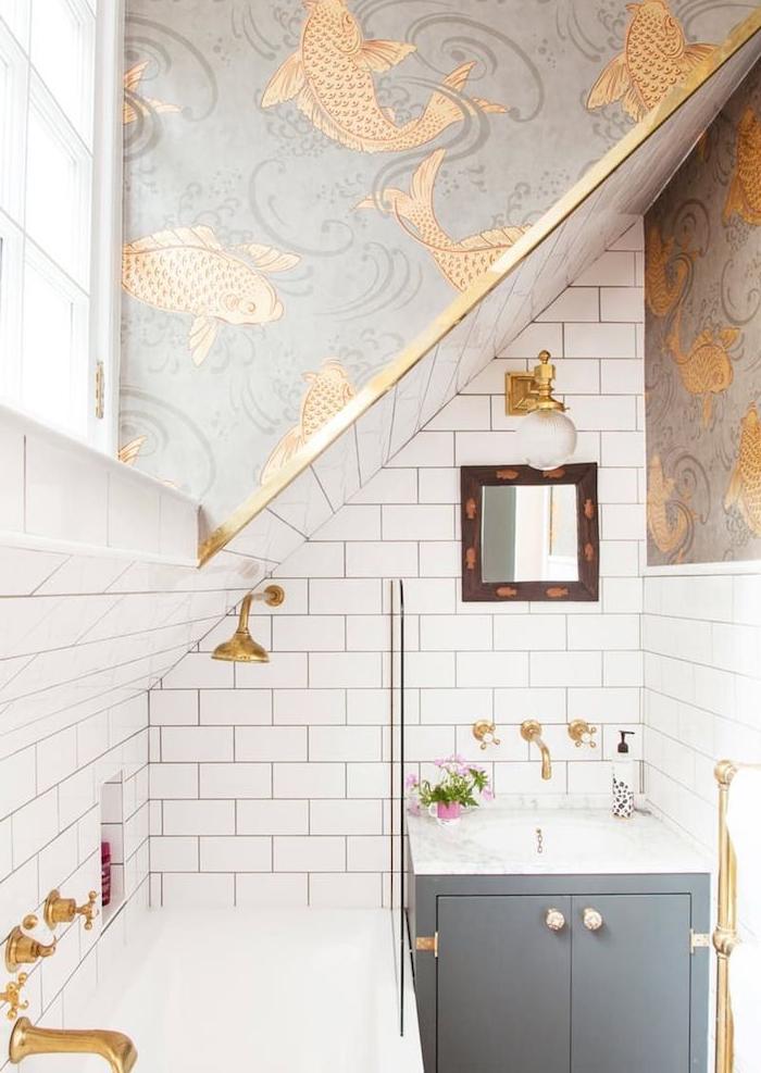 modele de baignoire sous pente avec murs papier peint original à poissons dorés, vasque dans meuble salle de bain gris, baignoire blanche, éléments en laiton