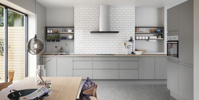 cuisine spacieuse au plafond blanc et plancher gris clair aménagée avec armoires gris clair et plan de travail bois