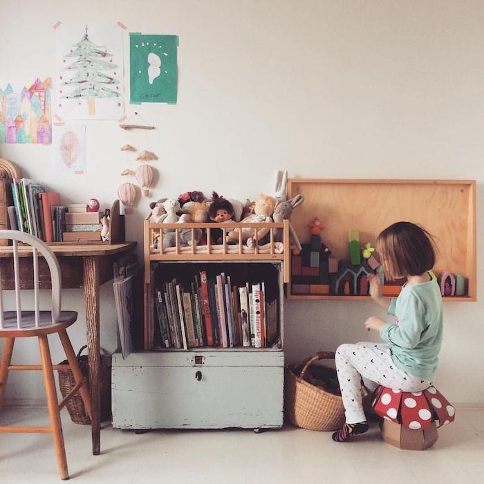 mobilier bas retro chic dans la chambre enfant, enfant assis sur tabouret champignon, étagères bois basses contre mur blanc, chaise et bureau bois vintage