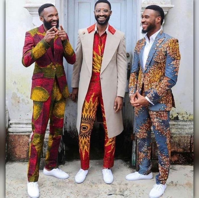 costumes en tissus africains, sneakers blancs, costumes colorés, longue veste beige combinée avec veste wax homme
