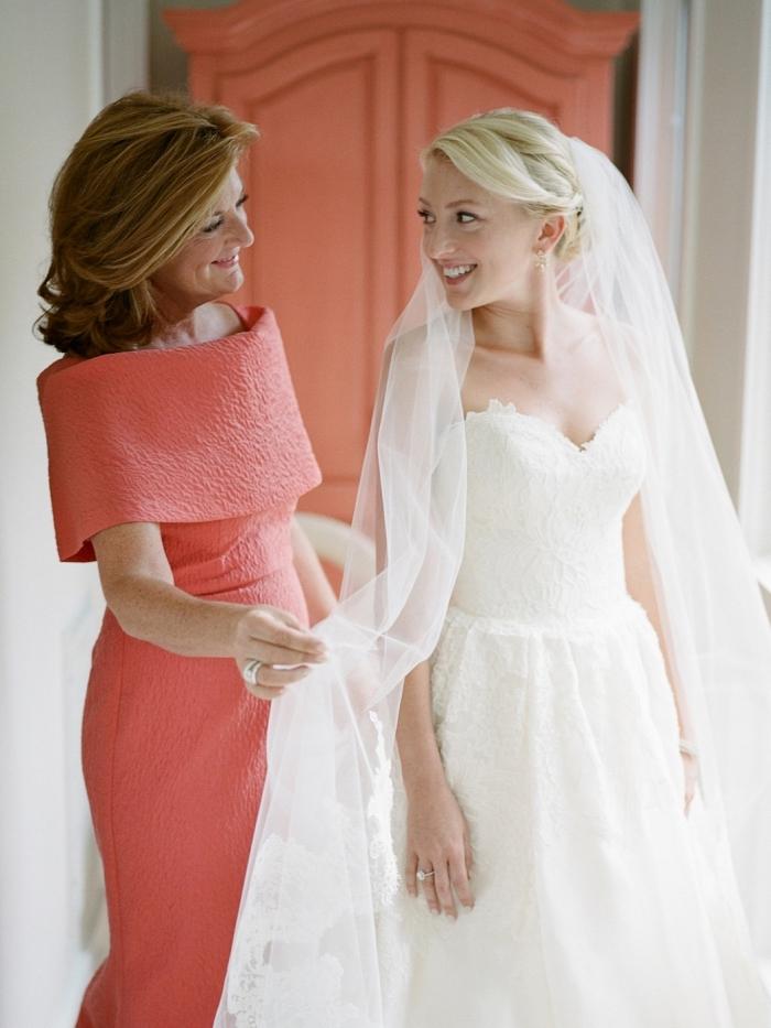 la mère de la mariée portant une robe longue couleur corail avec grande encolure bardot, robe de soirée cérémonie de mariage