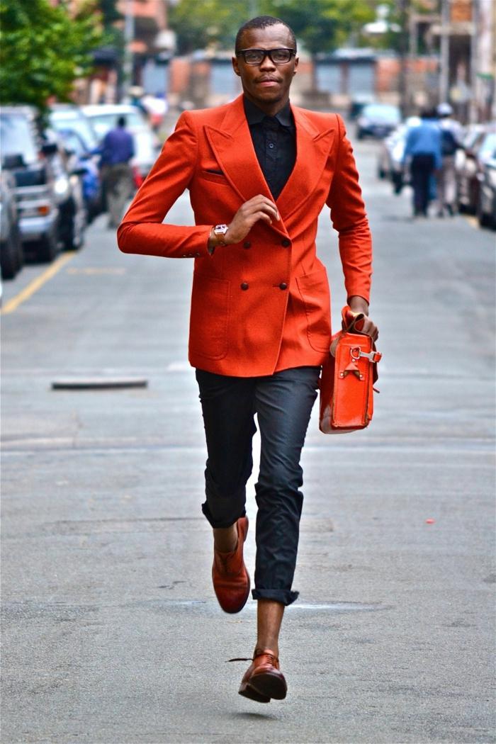 pantalon gris, chaussures de sport rouges, sac rouge, veste rouge, chemise bleu foncée, homme dans la rue