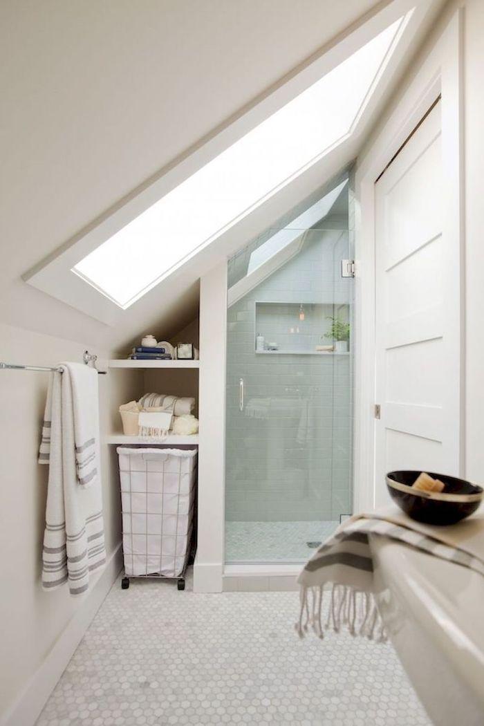 salle de bain 4m2 en blanc avec carrelage blanc au sol, douche miniature sous pente, lavabo design et grande fenêtre de toit