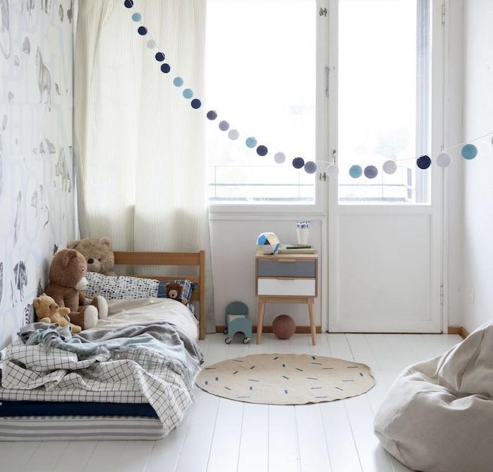 matelas ai sol couvert de linge de lit sur un parquet blanchi, murs blancs, guirlande de boules gris et bleu, barbaron gris