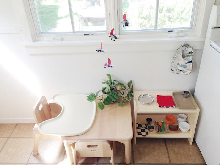 meuble vaisselle enfant avec chaise et table bois clair sur un carrelage marron dans la cuisine, murs blancs, espace à manger enfant