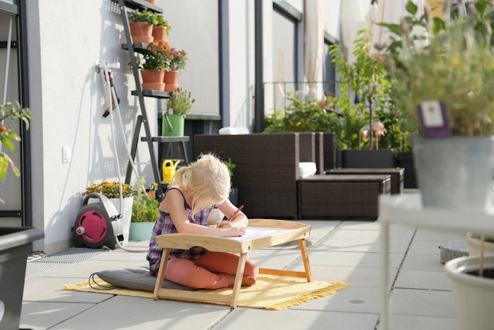 pédagogie montessori dans le jardin, table d'activité pour dessiner dans le jardin, coussin gris, tapis de jeu jaune
