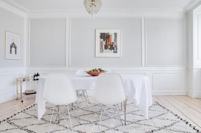 une salle à manger blanche de style vintage scandinave avec des moulures d'esprit classique qui donne du relief aux murs sans alourdir la déco, habillage mur intérieur bois tendance