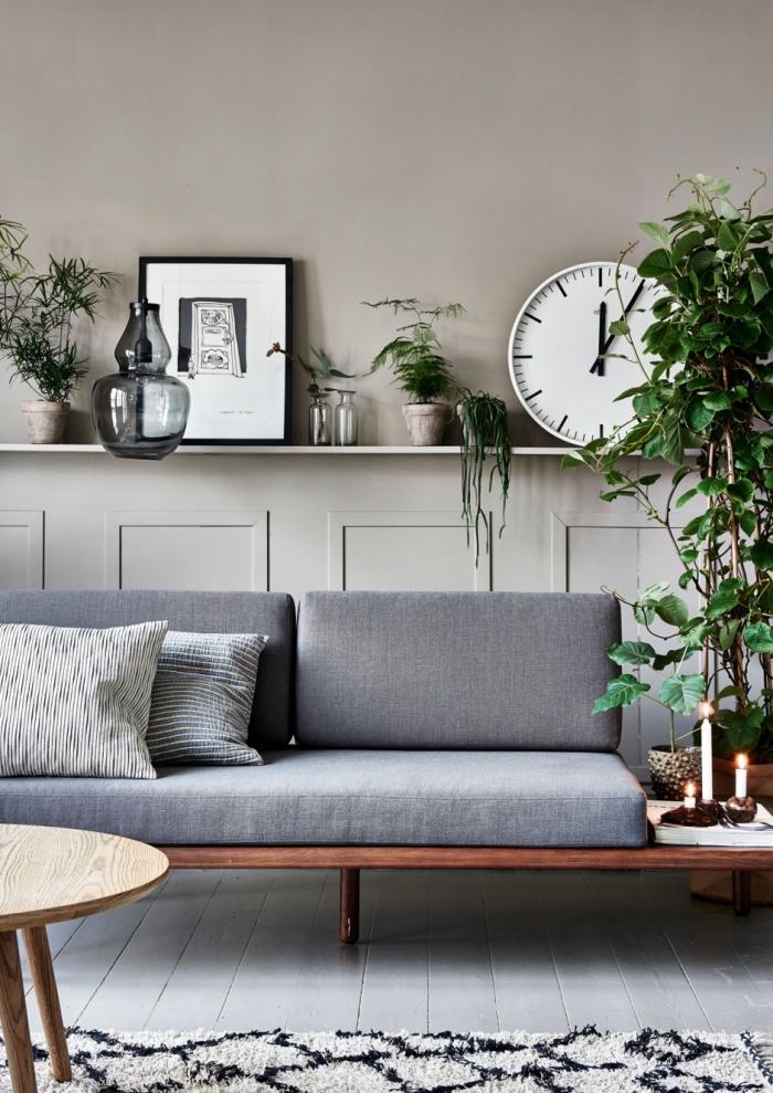 des panneaux décoratifs peints en gris clair pour habiller un mur du salon et lui donner du relief, soubassement décoratif en bois avec espace rangement pour ranger des plantes et de petits objets déco
