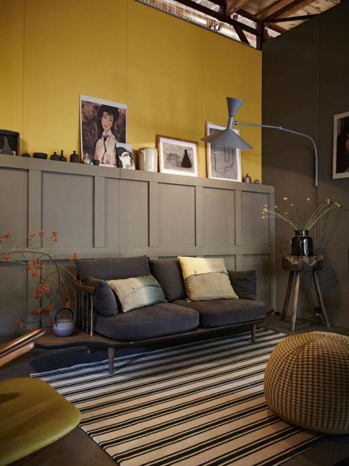 un mur bicolore décoré avec des caissons en bois posés en soubassement et repeints en couleur taupe, en joli contraste avec la peinture murale jaune moutarde