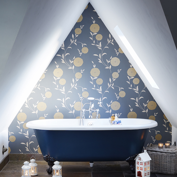 baignoire bleu nuit au milieu d une salle de bain mansarée avec mur d accent bleu à motifs floraux, lanternes lumineuses, panier de rangement