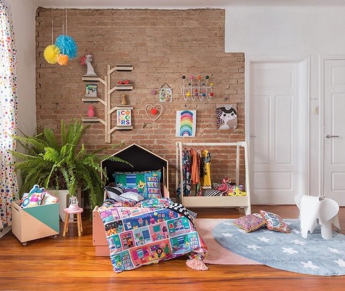 mur de briques decorative avec sol parquet bois, tapis rose et tapis rond, coffre à jouets à roulettes, dressing ouvert enfant