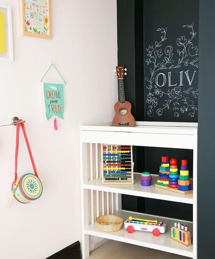 mur en peinture ardoise pour que l enfant puisse dessiner dessus, meuble rangement bas pour jouets, mur blanc décoré de dessins et decorations enfant