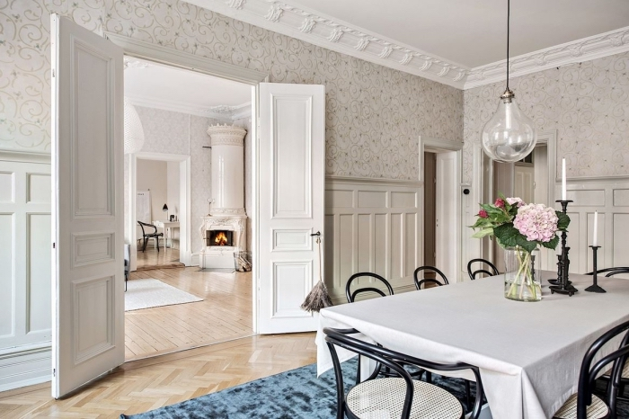 une salle à manger d'esprit vintage scandinave, habillage mur intérieur bois et papier peint
