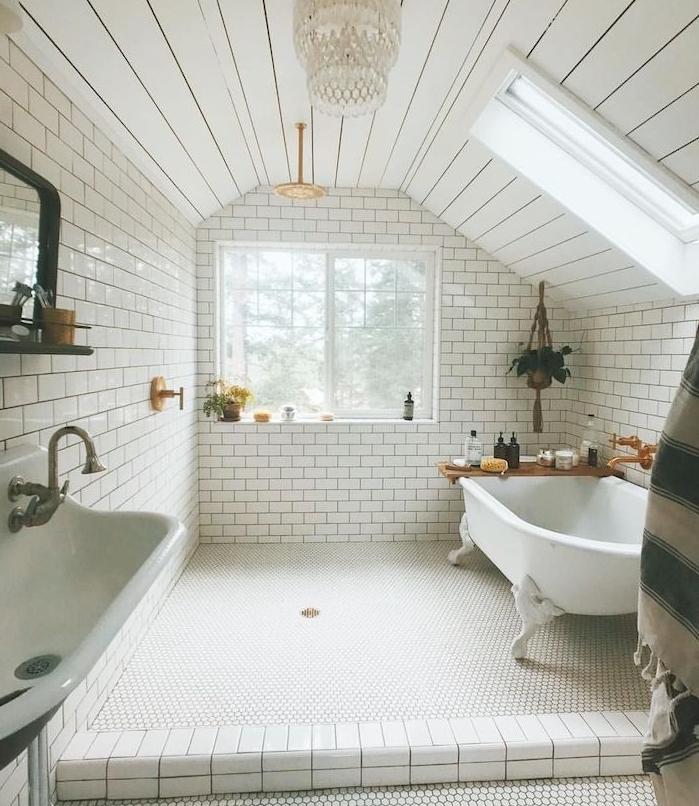 carrelage metro blanc dans une salle de bain mansardée style retro cic, baignoire blanche, pot de fleur suspendu macramé, lustre élégant