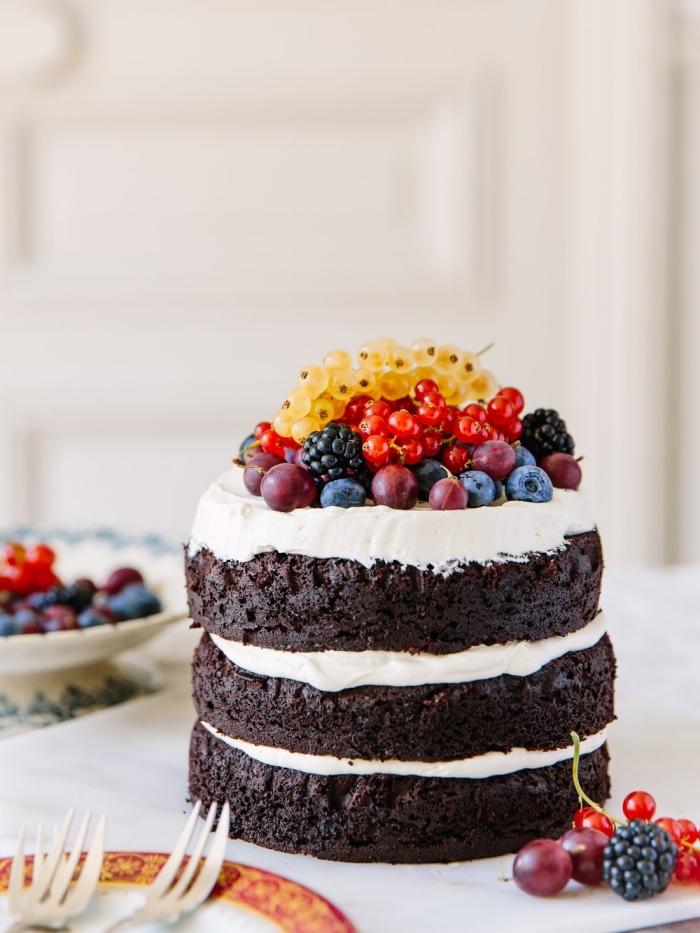 naked cake de trois génoises au chocolat fourré de glaçage blanc et décoré de fruits rouges et de groseilles