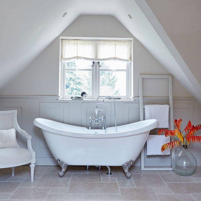 salle de bain gris et blanc avec baignoire blanche et accents argentés, branches à feuilles orange dans un vase, petites fenêtres avec voile blanche