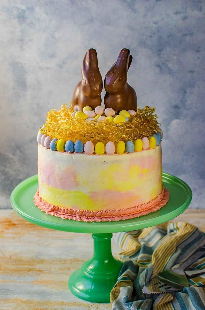 joli gâteau spécial pâques au glaçage dégradé en rose et jaune décoré d'un nid de paques en caramel et de deux lapins en chocolat