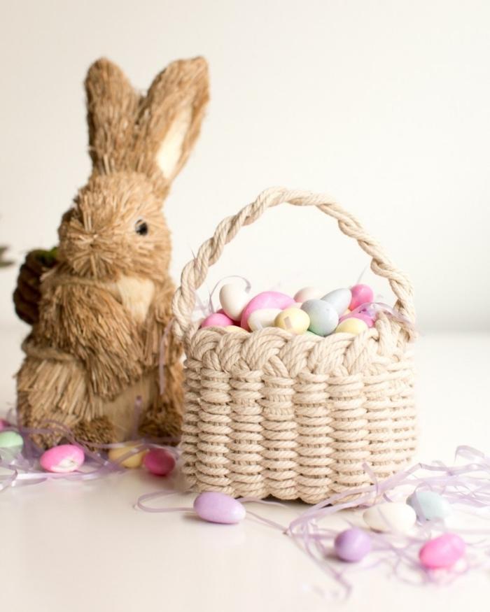 bricolage de paques, modèle de panier tressé rempli de oeufs peints de couleurs pastel, figurine lapin pour deco table paques