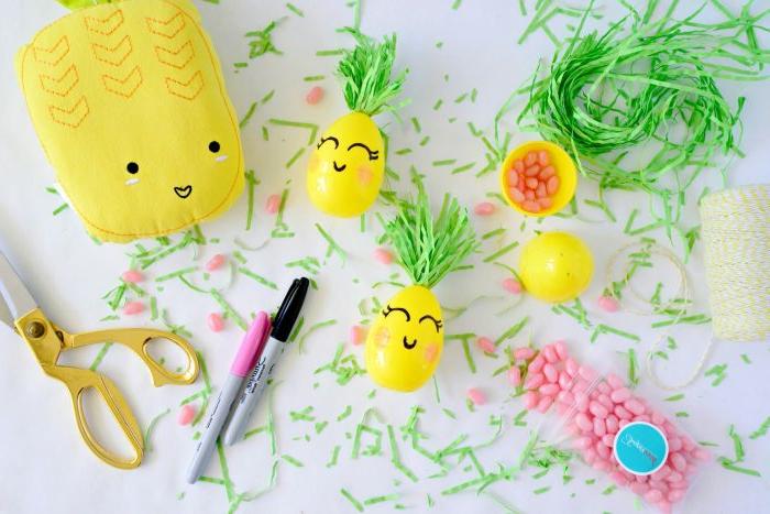 petits oeufs plastiques remplis de bonbons roses, herbe en papier, ciseaux, marqueurs
