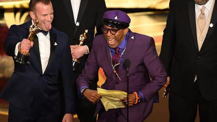 Photo de Spike Lee avec son costume violet en hommage à Prince qui remporte son premier Oscar du Meilleur Scénario Adapté pour BlacKkKlansman