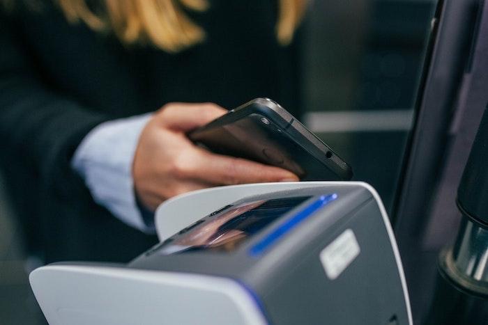 femme avec portable dans la main en traine de faire un paiement de téléphone
