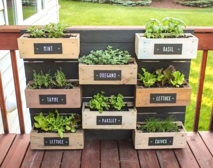 des aromatiques plantées dans une jardinière en palette avec des bacs à planter à niveaux différents, idée pour aménager un petit jardin en hauteur avec une palette recyclée