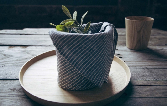 serviette en tissu graphique pliée en petit panier, modèle de pliage origami paques facile et rapide pour décorer une table de style rustique