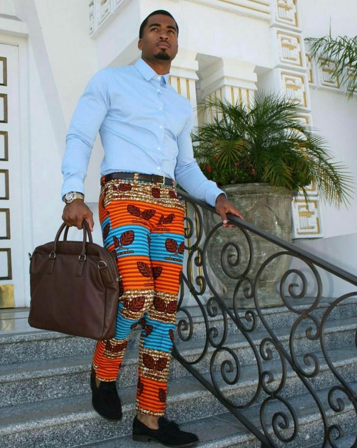 pantalon africain homme, chemise bleu claire, sac marron, mocassins noirs, rambarde fer forgé, bâtiment blanc