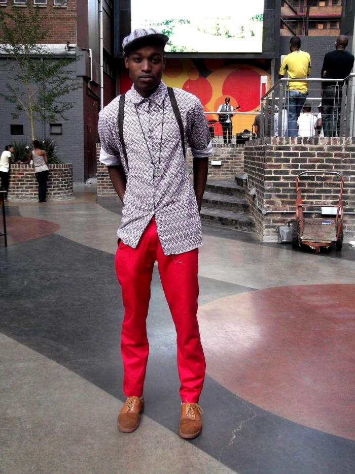 vetement africain homme, pantalon rouge, chemise bleu claire aux motifs graphiques, casquette bleu clair, chaussures marron