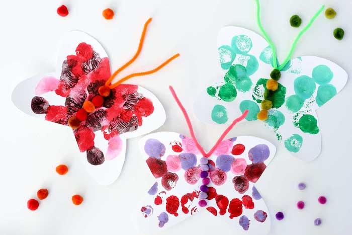 papillon a faire soi meme en papier blanc avec deco d empreintes de doigt et centre en pompons colorés, antennes en cure pipe