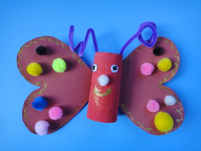 papilon en rouleau de papier toilette rempeint de rouge, ailes de papier décorés de paillettes et pompons colorés