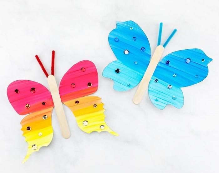 faire une papillon aux ailes de papier colorés et corps en batonent de glace décoré de strass, antennes en cure pipe